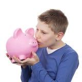Cute boy kissing pink piggybank Stock Photo
