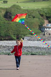 Cute boy with kite on the beach Stock Images