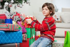 Cute Boy Kneeling By Christmas Gifts Royalty Free Stock Images