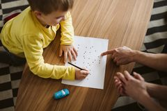 Cute boy kneeling on the floor and connecting dots on a piece of paper. Cute boy kneeling on the floor and connecting dots on piece of paper royalty free stock photos