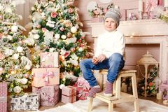 Cute boy in knitted hat and sweater Christmas Interior stock photos
