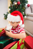 Cute boy in large christmas present drinking milk Royalty Free Stock Photography