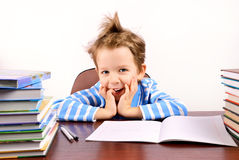 Cute boy laughing sitting at the desk. Many textbooks on the desk. light background.  horizontal Stock Photography