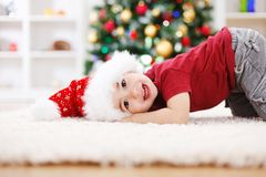 Cute boy laying in front of Chrismas tree Royalty Free Stock Photo