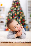 Cute boy laying in front of christmas tree Royalty Free Stock Photography
