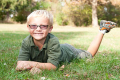 Cute Boy Laying in Grass. Cute young boy with glasses posing prone outdoors in the grass Royalty Free Stock Images