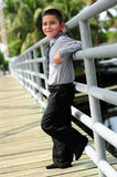 Cute Boy leanings against pole on bridge Stock Photo