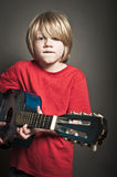 Cute boy learning an instrument Royalty Free Stock Images
