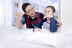 Cute boy learning to calculate with his father Stock Photos