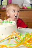 Cute boy licks frosting from fingers birthday cake Royalty Free Stock Images