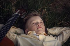 Cute boy lies on the grass with a guitar on sunset Stock Images