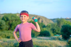 Cute Boy Lifting Dumbbell with Right Hand on Waist Royalty Free Stock Image