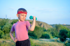 Cute Boy Lifting Dumbbell with Right Hand on Waist Stock Images