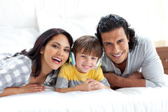 Cute boy listening to music with his parents. Cute little boy listening to music with his parents on a bed Stock Photo