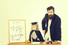 Cute child and bearded professor. Cute boy little child in squared hat and black academic gown sitting at desk near school blackboard with formulas and professor royalty free stock photography
