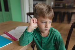 Cute boy looking away while sitting on dining table in a comfortable home. Front view of cute Caucasian boy looking away while sitting on dining table in a stock photography