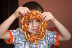Cute boy is looking through the hole of pancake Stock Images