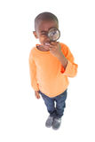 Cute boy looking through a magnifying glass Royalty Free Stock Photos