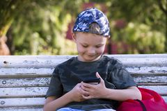 Cute boy looking mobile phone on bench. In summer Stock Photo