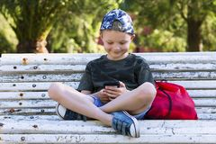 Cute boy looking mobile phone on bench. In summer Royalty Free Stock Photo