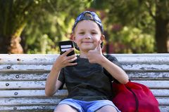 Cute boy looking mobile phone on bench. In summer Royalty Free Stock Image