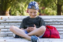 Cute boy looking mobile phone on bench. In summer Stock Photos