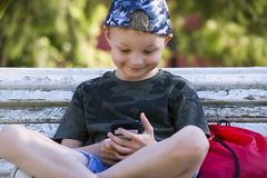 Cute boy looking mobile phone on bench. In summer Royalty Free Stock Photography