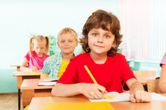Cute boy looking straight and writing with pen. In classroom with other students sitting at desks Royalty Free Stock Images