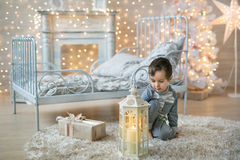 A cute boy looks at the lantern near the bed Royalty Free Stock Photos