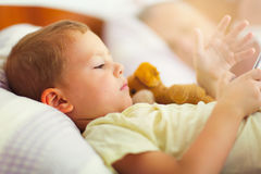 Cute boy lying on the bed and use the phone Royalty Free Stock Image