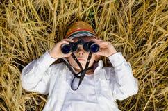 Cute boy lying down in a field of ripe wheat Stock Photos