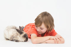 Cute boy lying down while looking at bunny Stock Image