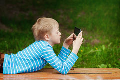 Cute boy lying in park and using tablet pc Stock Photo