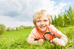 Cute boy with magnifier laying on the green grass Stock Photography