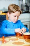 Cute boy making cupcakes Stock Image