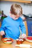 Cute boy making cupcakes Stock Photography