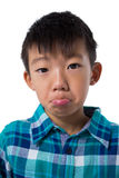 Cute boy making faces against white background Royalty Free Stock Images