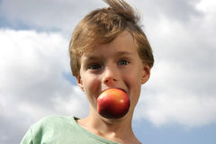 Cute boy making fun with a peach royalty free stock photo