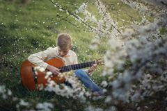 Cute boy making music playing the guitar on nature. Stock Images