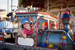 Cute boy on a merry-go-round carousel, riding a train Stock Photo