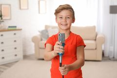 Cute boy with microphone in room stock image