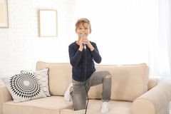 Cute boy with microphone on sofa in room royalty free stock image