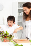 Cute boy mixing a salad with his mother Royalty Free Stock Photos