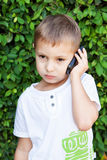 Cute boy with mobile phone. Cute boy talking on mobile phone on the background of green leaves bush Royalty Free Stock Photos