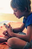 Cute boy with mobile phone. At home Stock Images