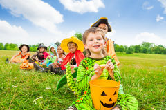 Cute boy in monster costume holds Halloween pail Royalty Free Stock Photos