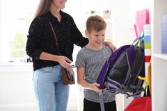Cute boy with mother choosing backpack royalty free stock image