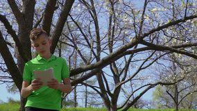 Cute boy holding notebook leans on tree in the park. Cute boy with notebook leans on tree in the park. The boy reads something in his notebook. Camera in motion stock video