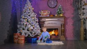 Cute boy opening presents on Christmas evening. HD. stock video footage