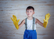 Cute boy in oversized rubber gloves Stock Image